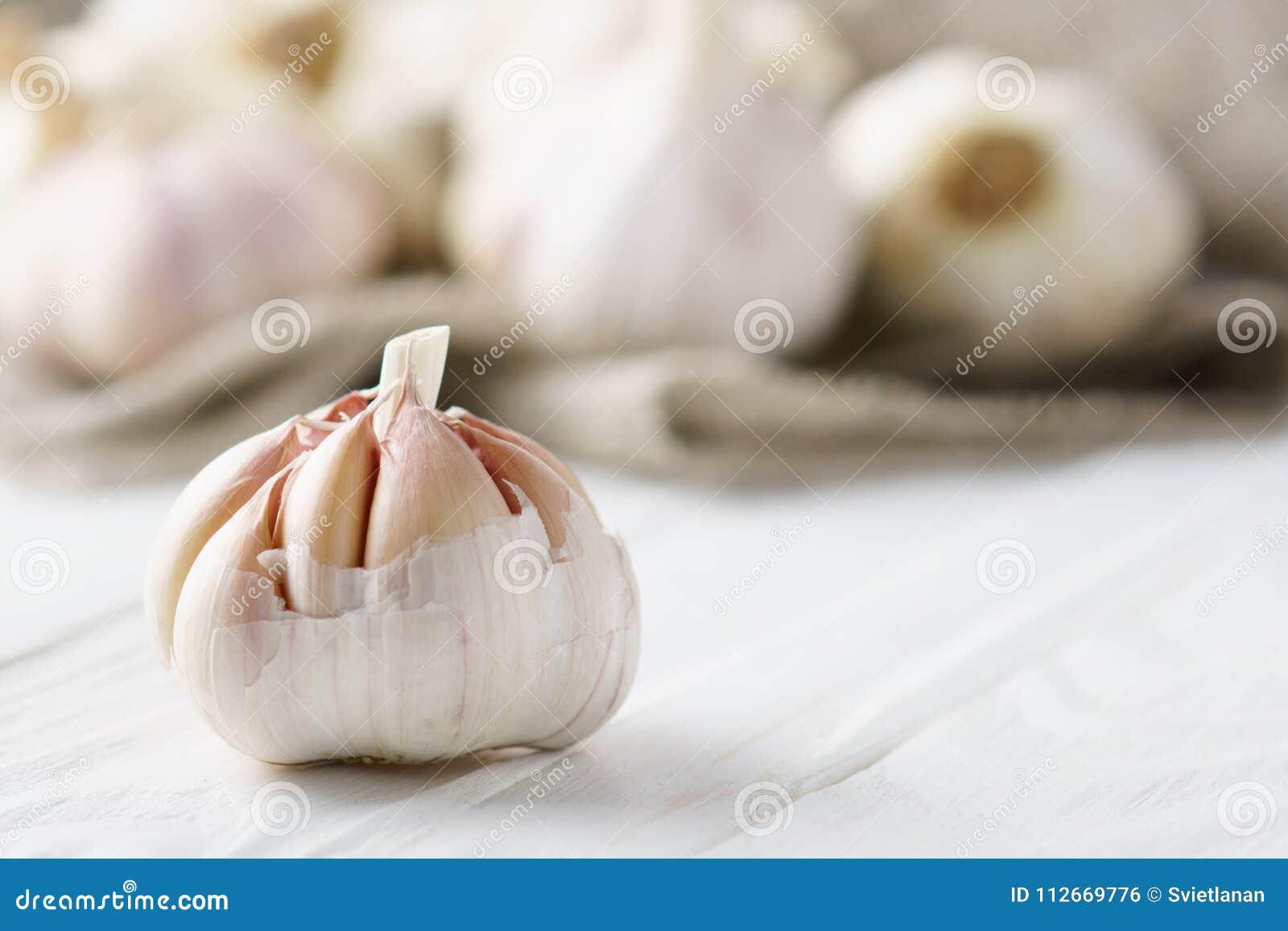 Bulbo do alho no fundo de madeira branco