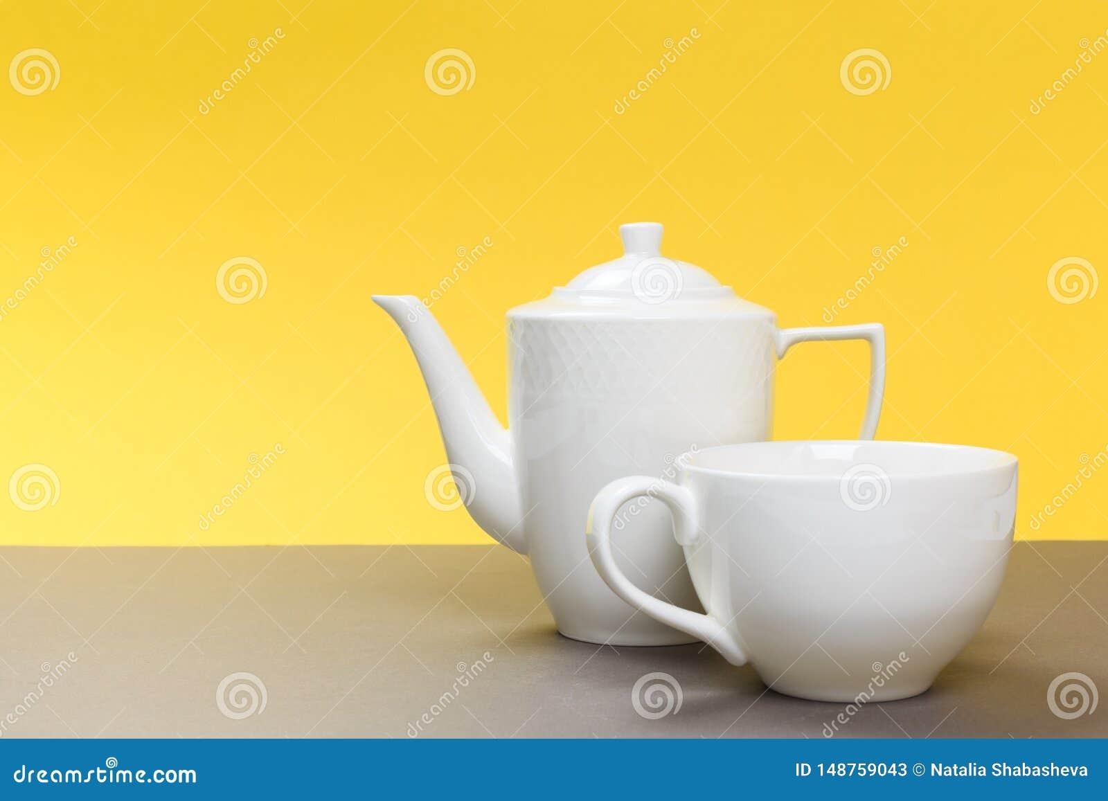 Bule e copo brancos da porcelana do vintage na placa cinzenta e no fundo amarelo