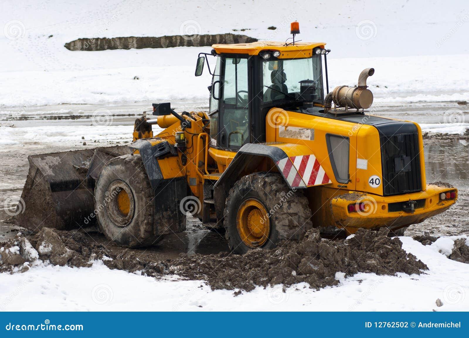 Bull dozer deep in mud and snow