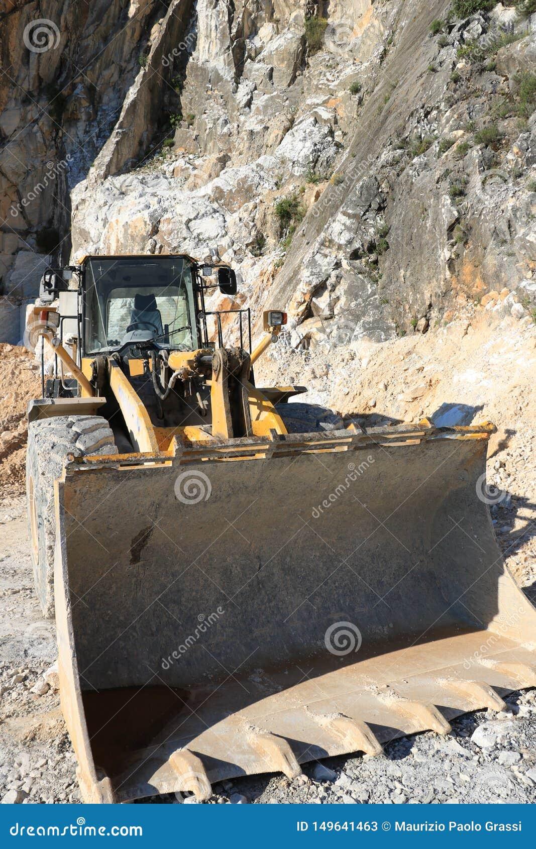 Bulldozer in a Carrara marble quarry. A large mechanical shovel