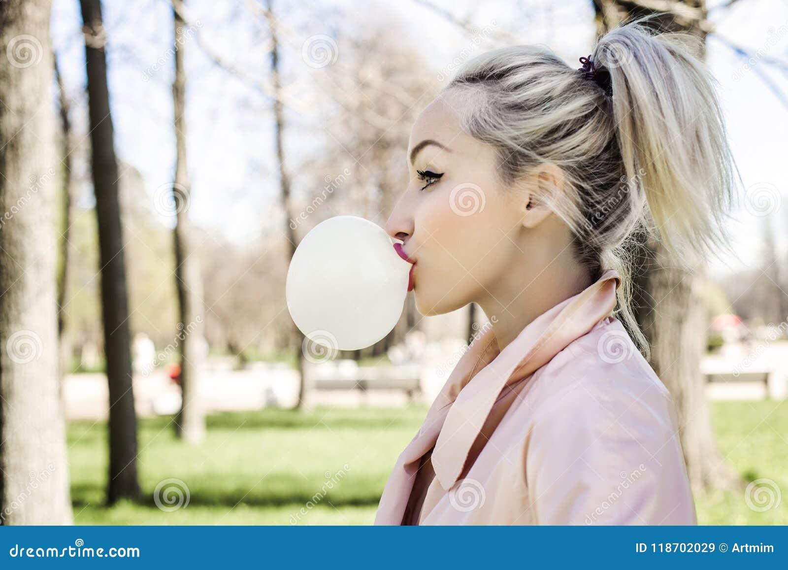 Bulle de soufflement de jeune femme avec le chewing-gum