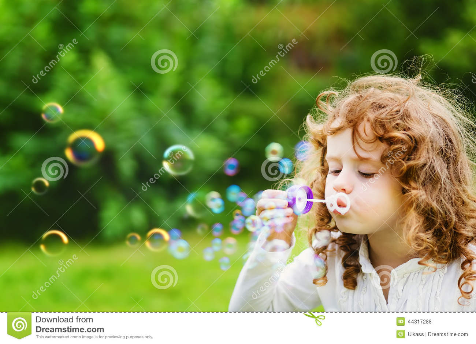 Bulles de savon de soufflement de petite fille
