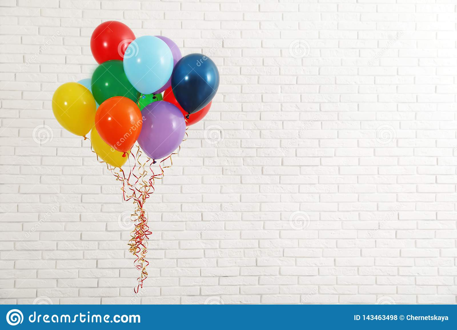Bunch of bright balloons near wall, space for text. Celebration time