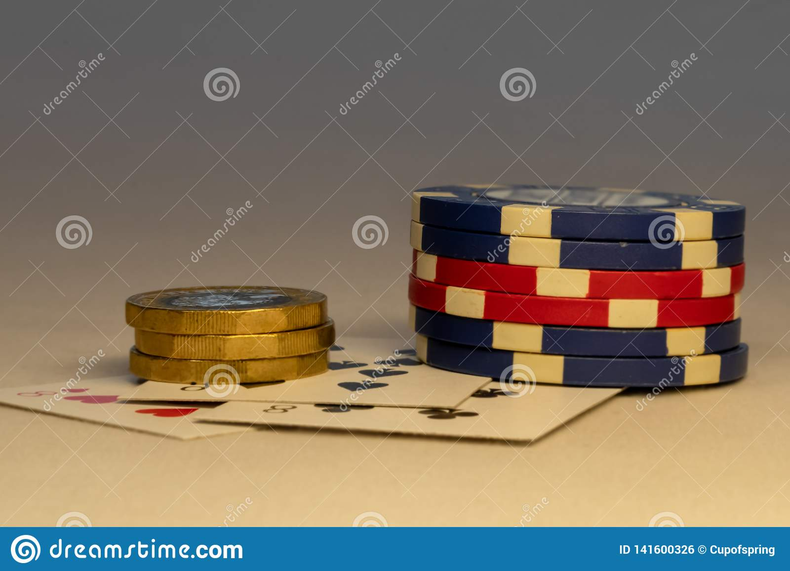 Bunch of chips laying down on table with coins and cards in the background. Casino and gambling concepts