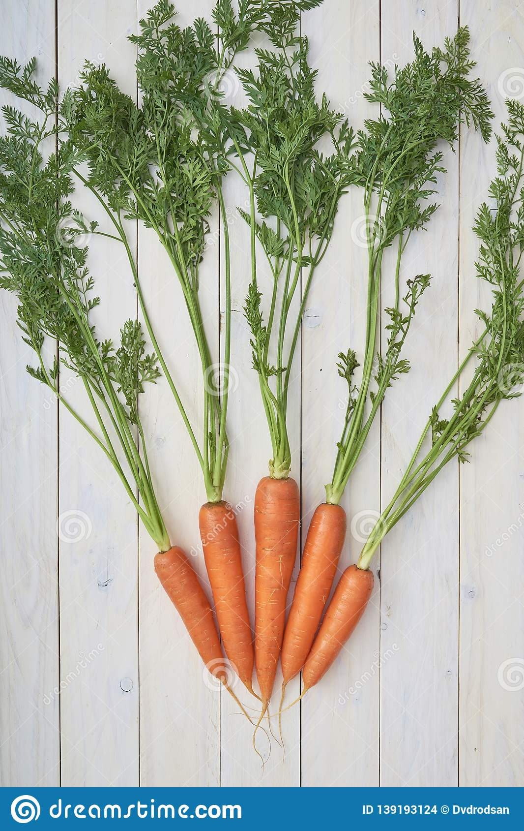 Bunch of fresh carrots with green leaves over white wooden background. Veggies. Organic vegetables. Natural farm products