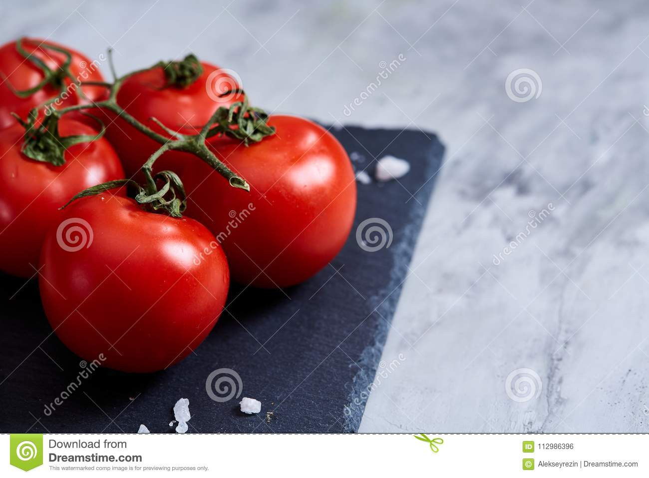 Bunch of fresh tomatoes with green leaves on stony board over white background, top view, close-up, selective focus