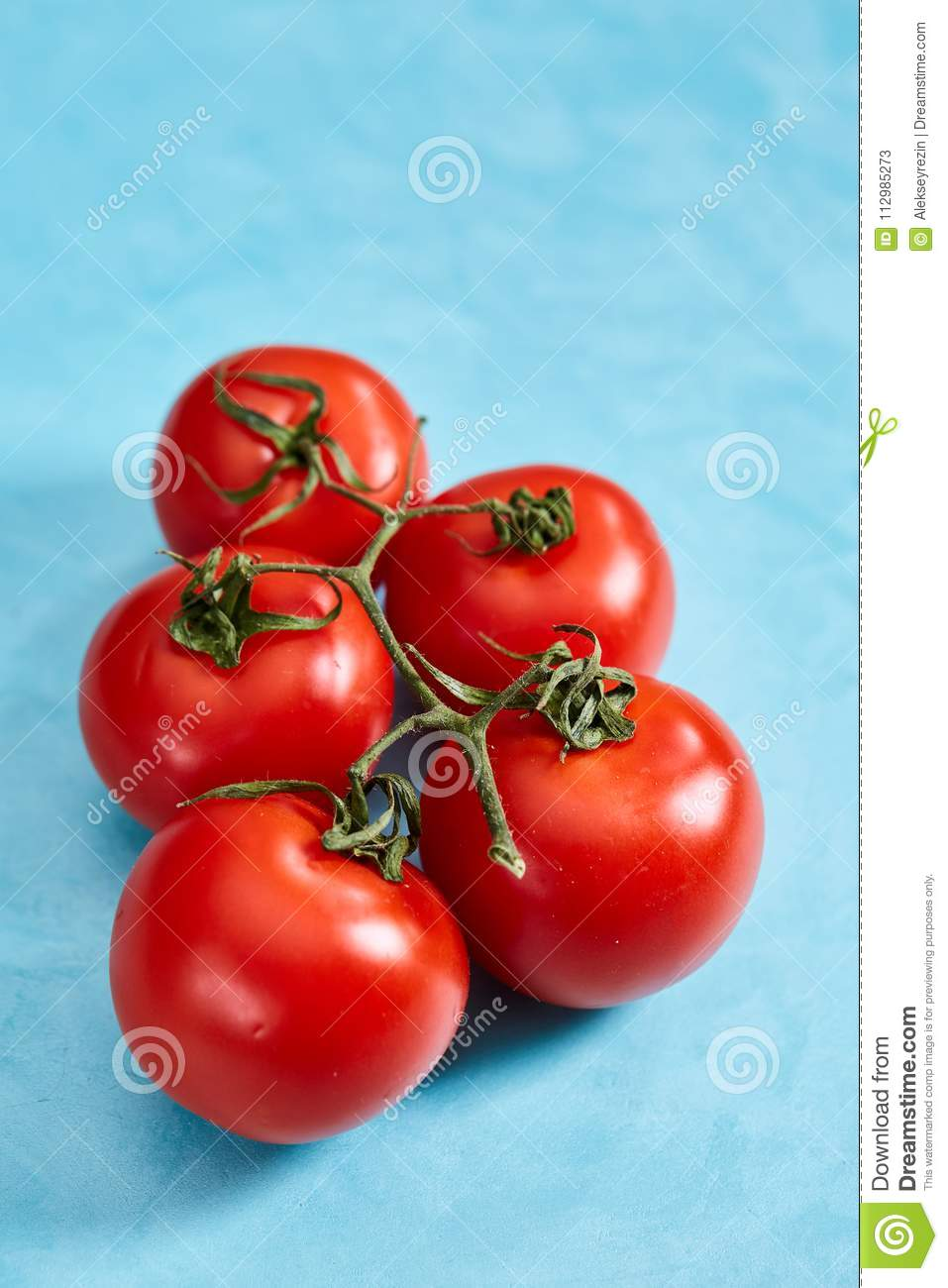 Bunch of fresh tomatoes with green leaves isolated on blue background, top view, close-up, selective focus
