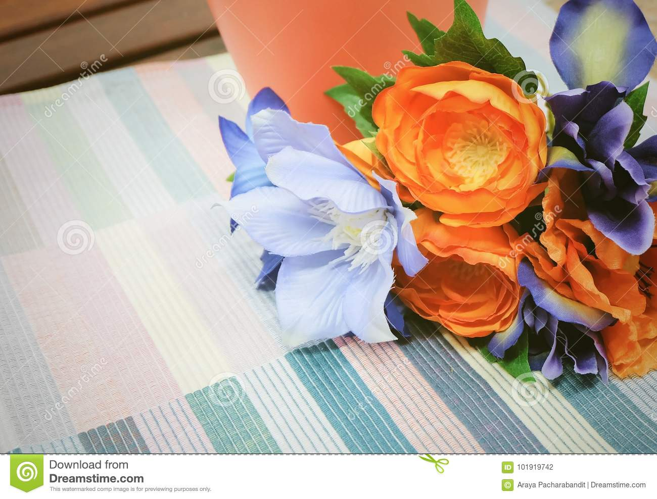 Bunch Of Orange Artificial Ranunculus With Blue Flowers Stock Photo
