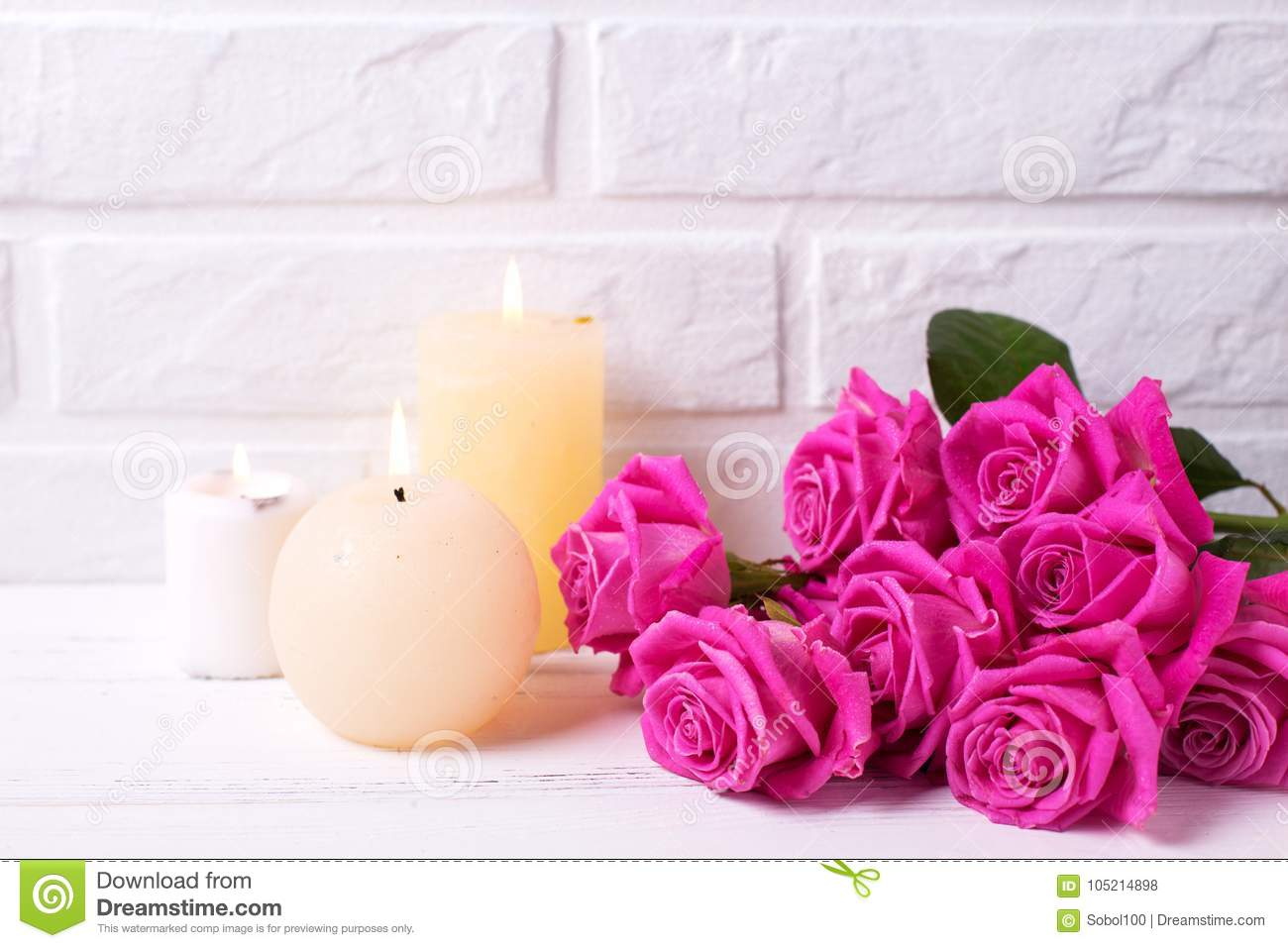 Bunch Of Pink Roses Flowers And Three Burning Candles On Whit Stock