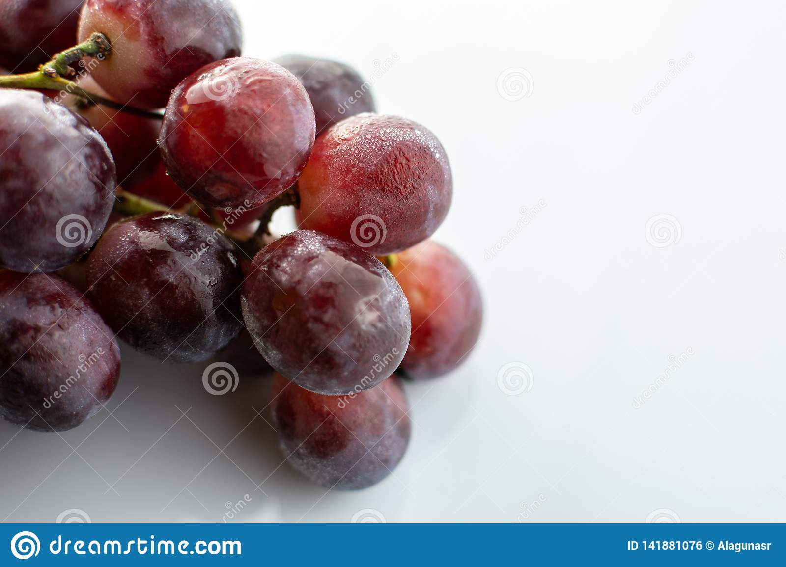 Bunch of red wet grapes isolated on white background