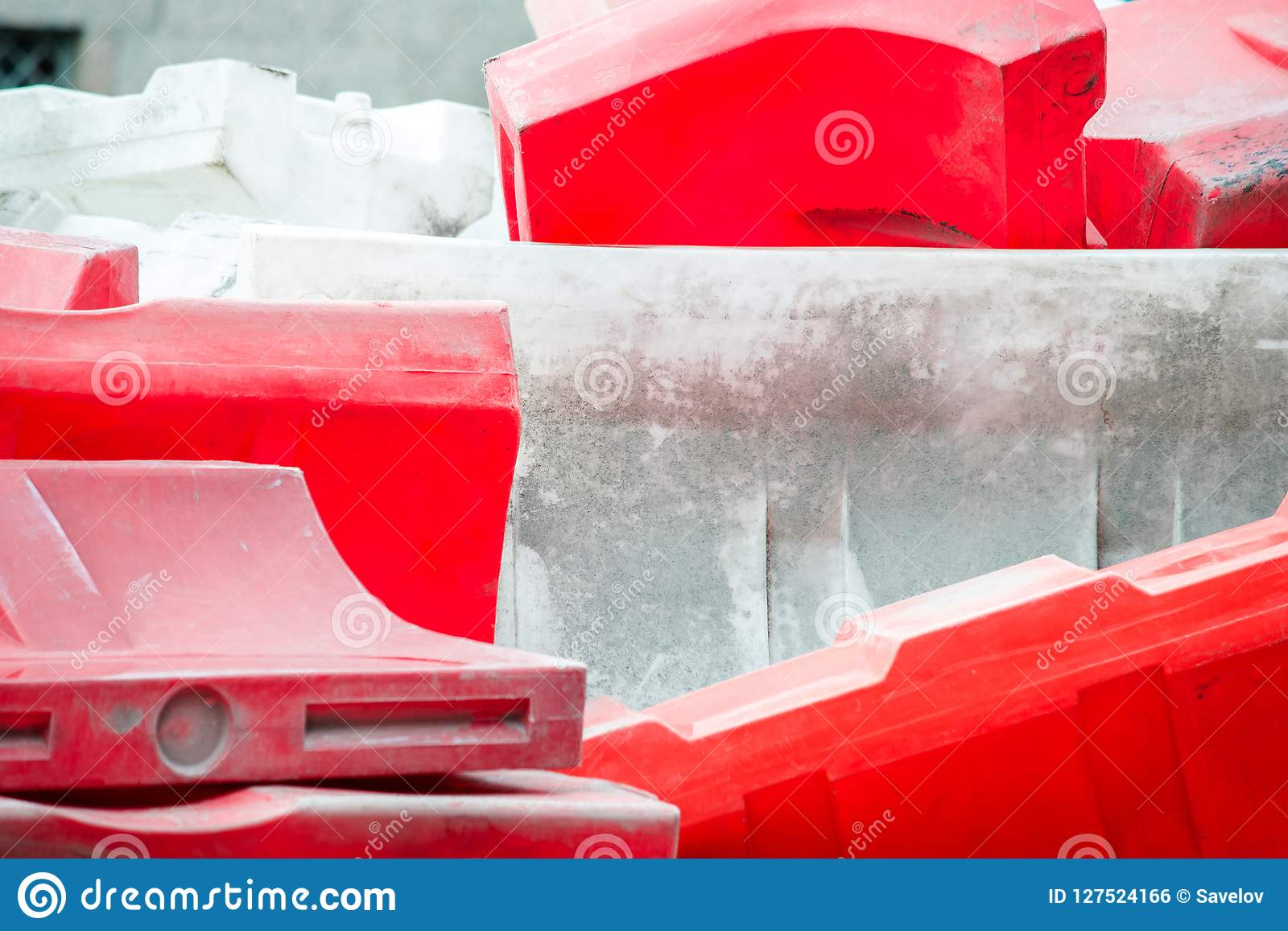 A Bunch Of Red And White Water-filled Plastic Road Barriers