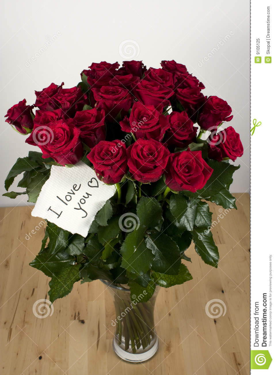 a bunch of roses in glass vase with love card royalty free