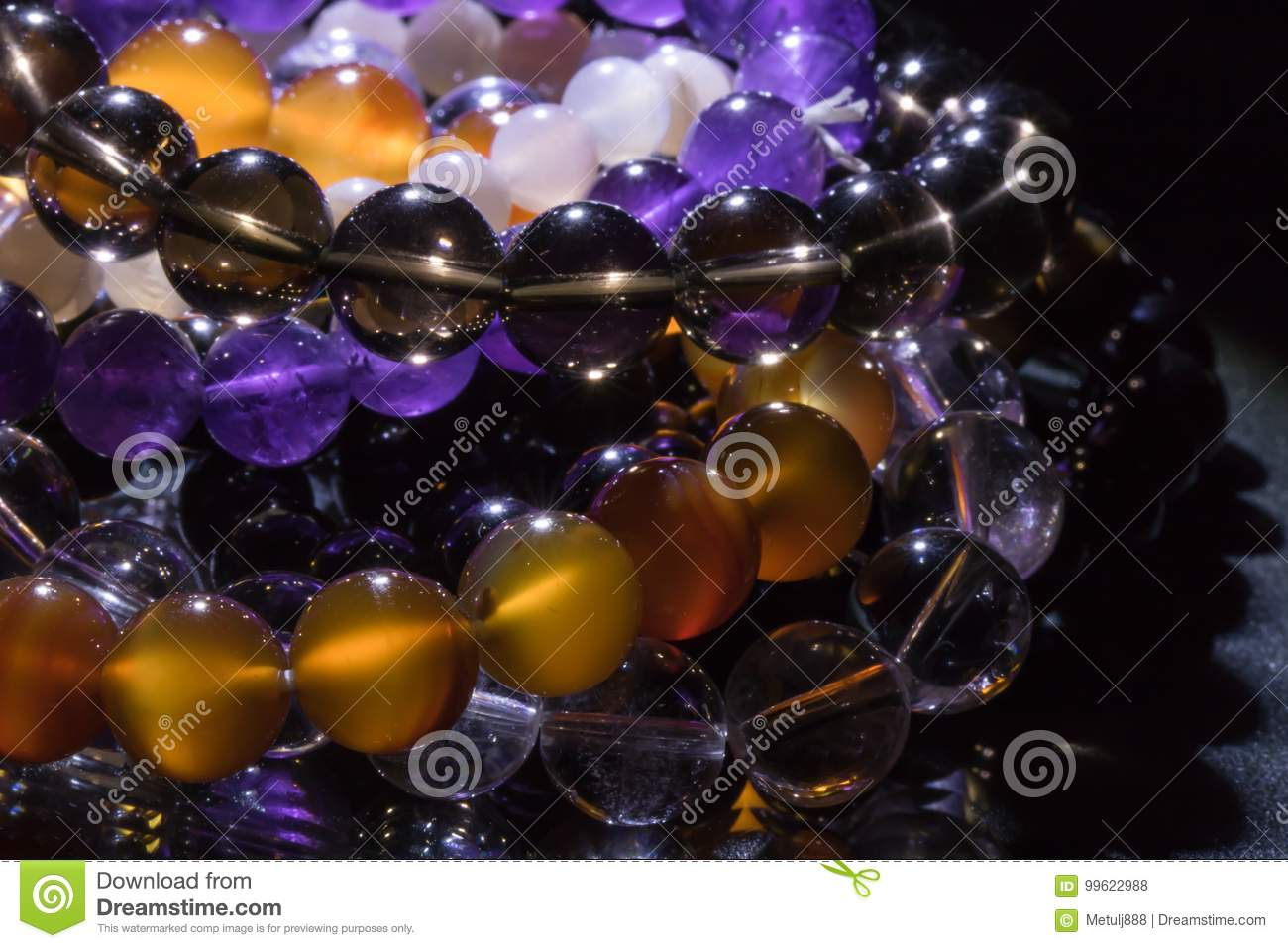 Bunch of semiprecious gemstone bracelets on black background - cornelian, amethyst, quartz