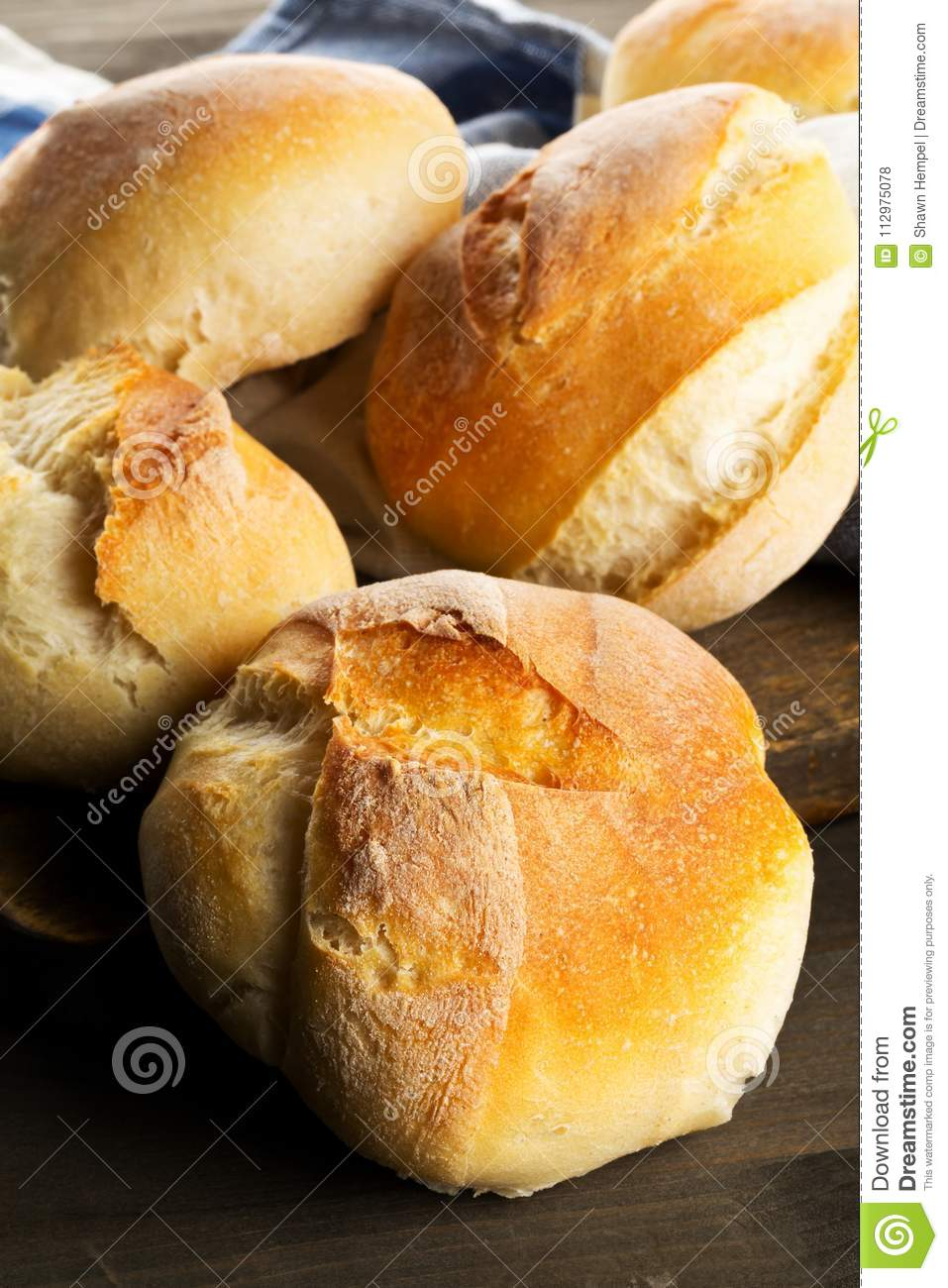 Bunch of whole, fresh baked wheat buns on dark wooden table