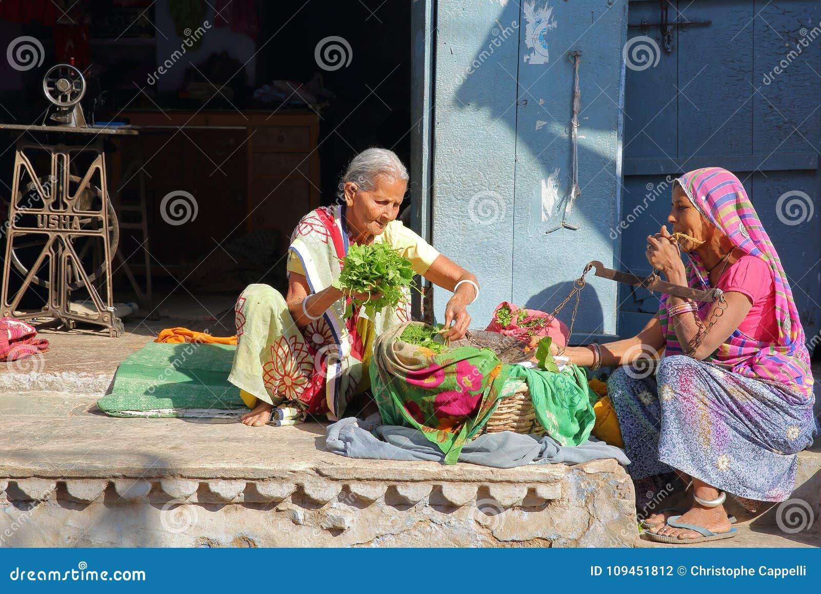 BUNDI, РАДЖАСТХАН, ИНДИЯ - 10-ОЕ ДЕКАБРЯ 2017: Красочная сцена с 2 старухами, одно улицы из их держа традиционную пару s