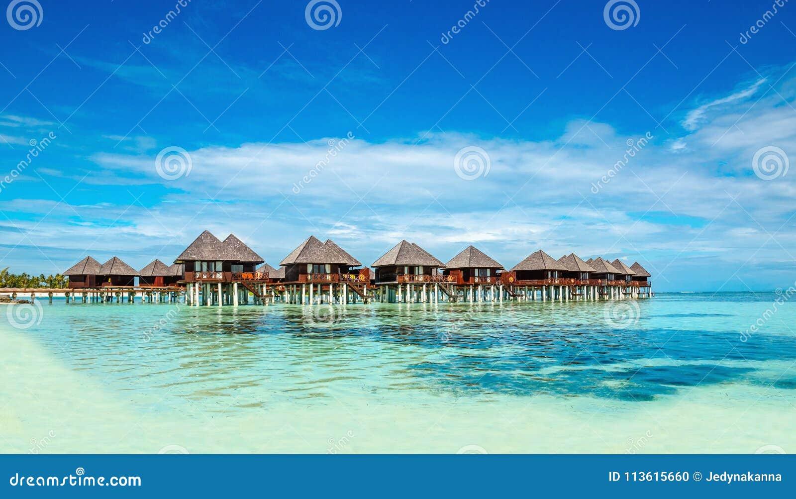 Bungalow di legno sui precedenti di acqua e di cielo blu azzurrati, Maldive