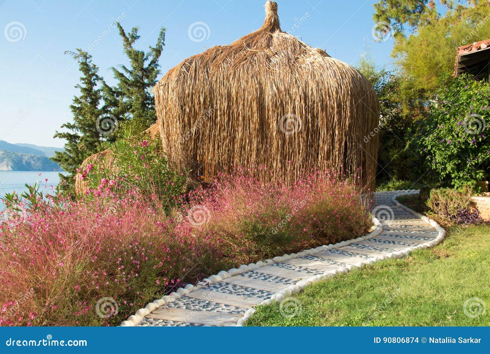 Bungalow tropicali legnosi con il tetto ricoperto di paglia vicino alla spiaggia