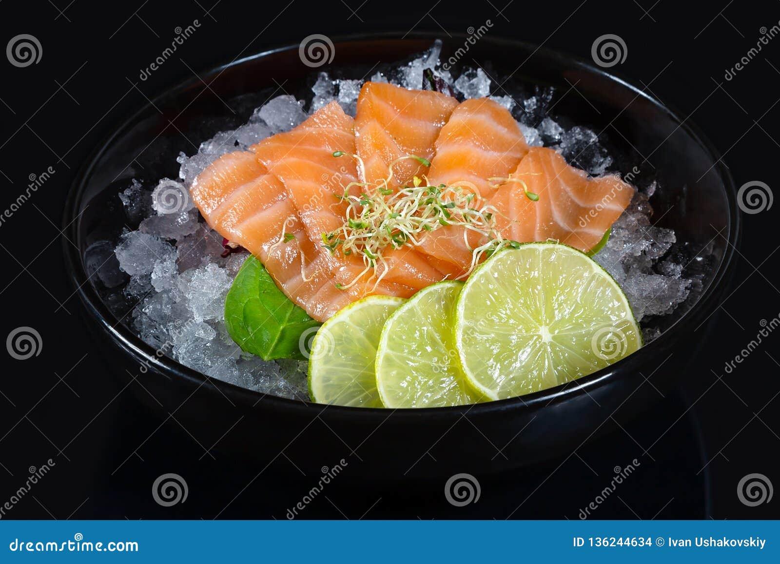Bunke av den nya japanska sashimien av laxen med limefrukt på is