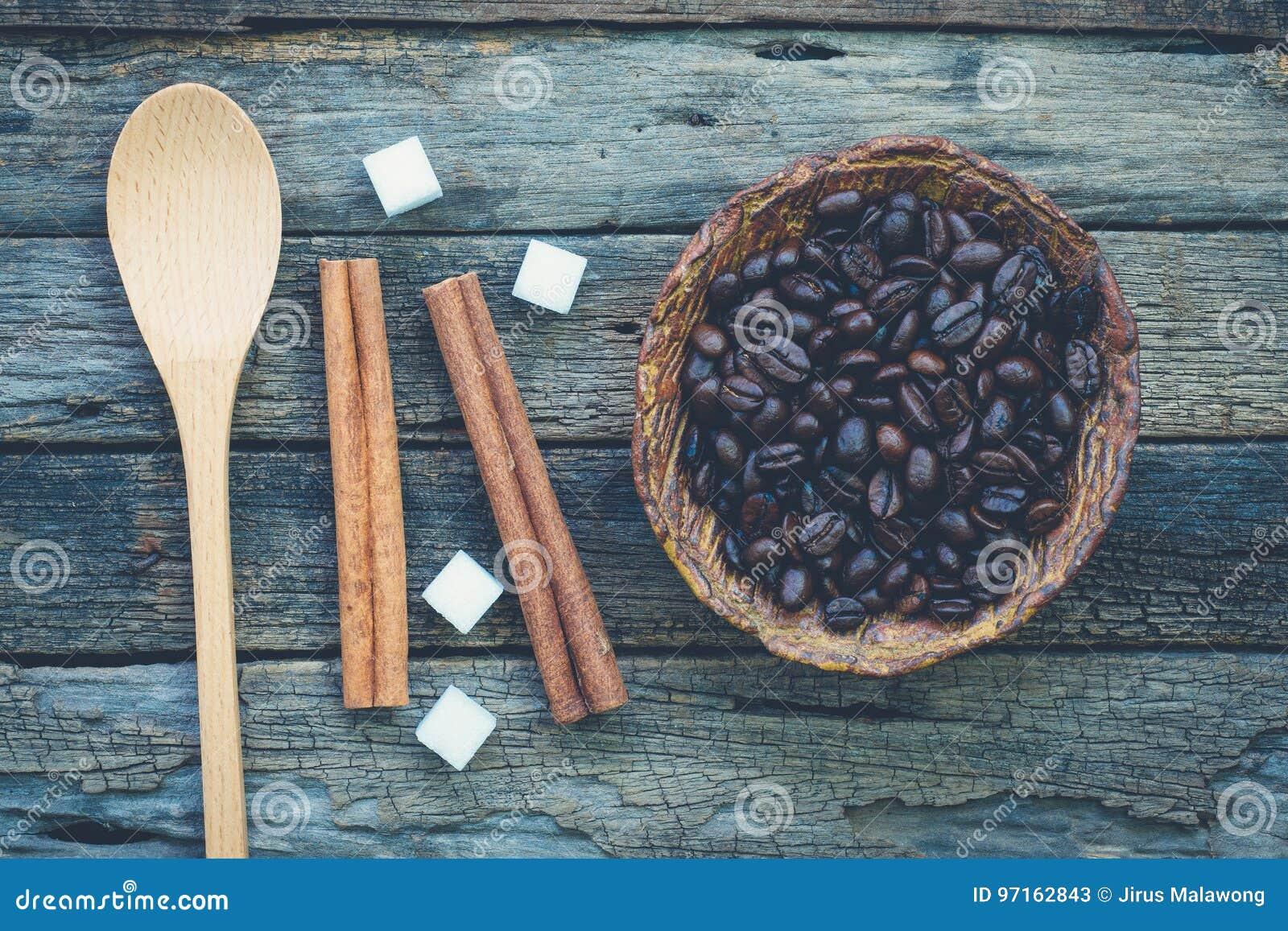 Bunke av grillade kaffebönor och en sked med kanelbruna pinnar