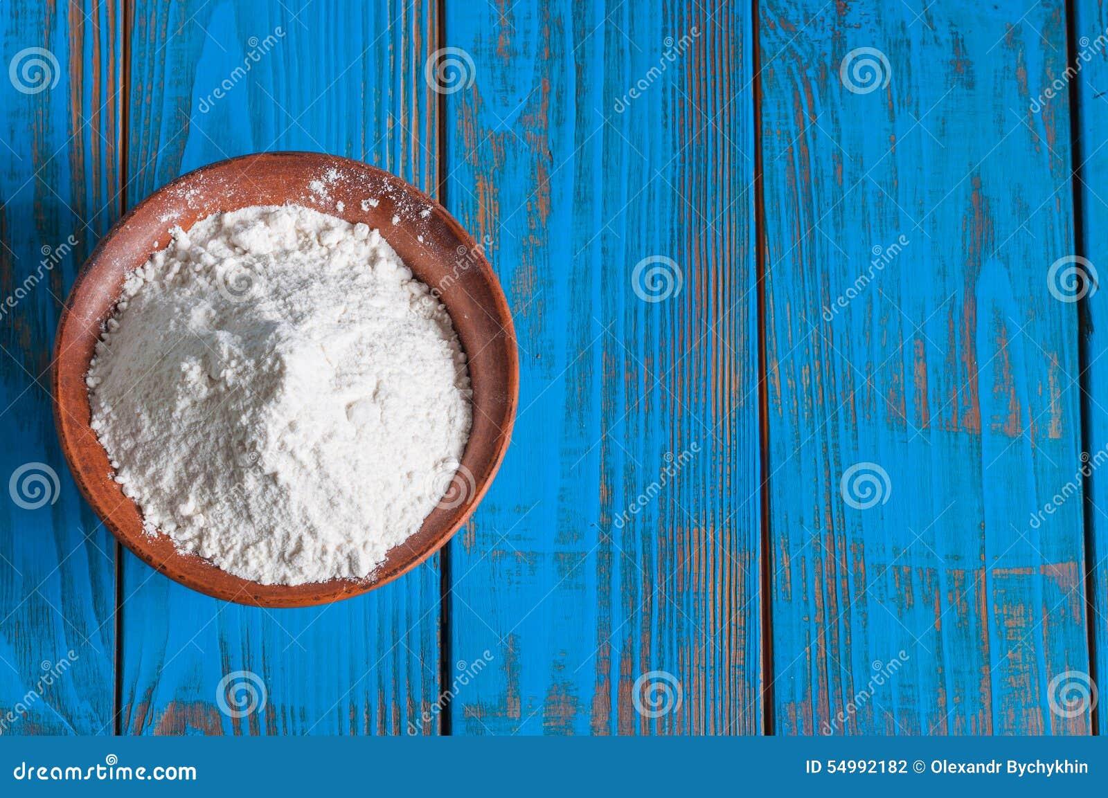 Bunke av vetemjöl på den wood tabellen för tappning från
