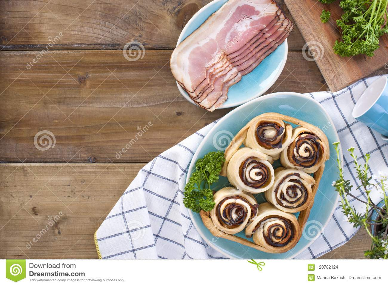 Buns with bacon and fresh herbs for lunch. Blue dishes. Wooden background and free space for text.