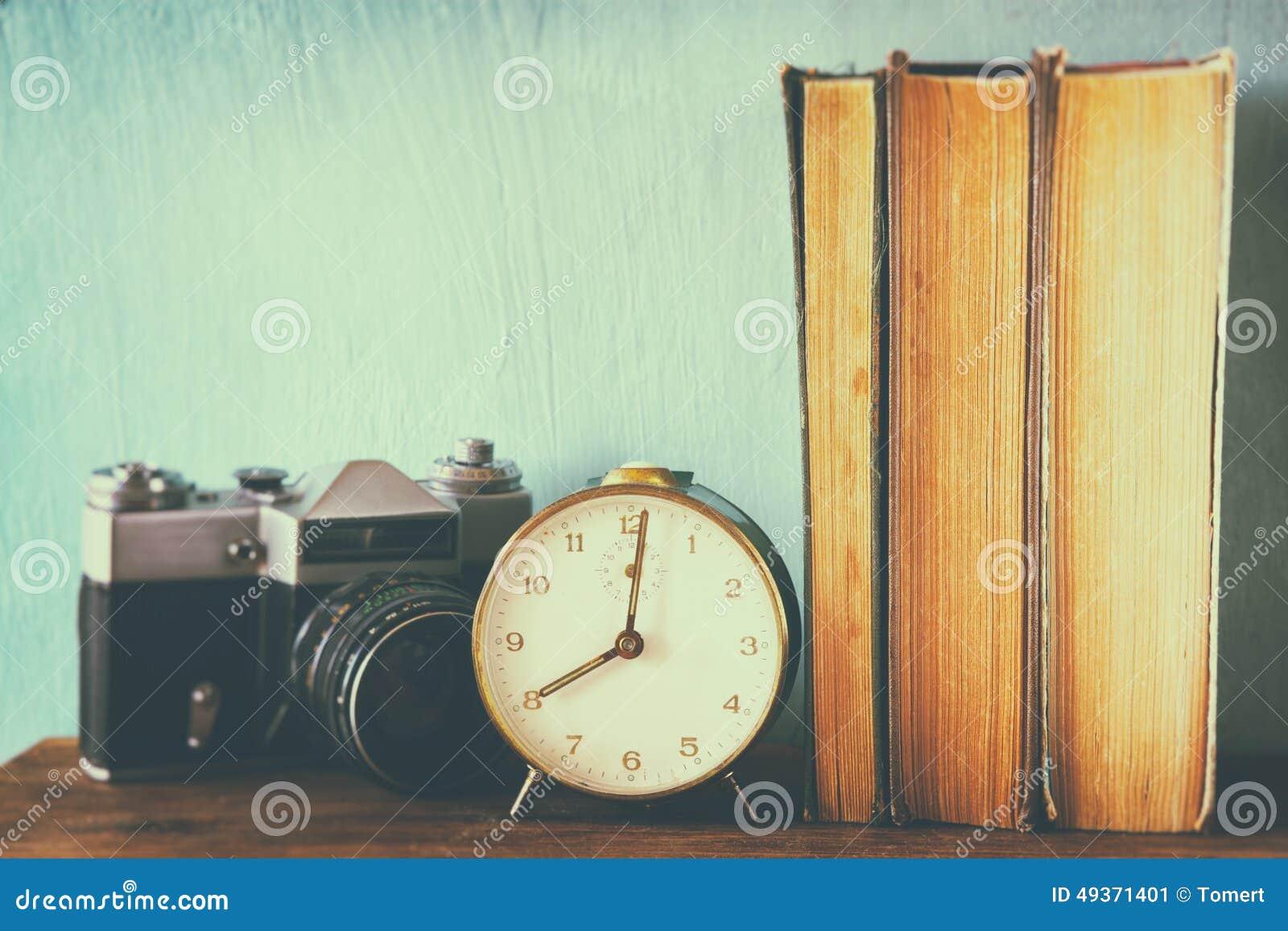 Bunt av böcker, den gamla klockan och tappningkameran över trätabellen bilden bearbetas med retro urblekt stil
