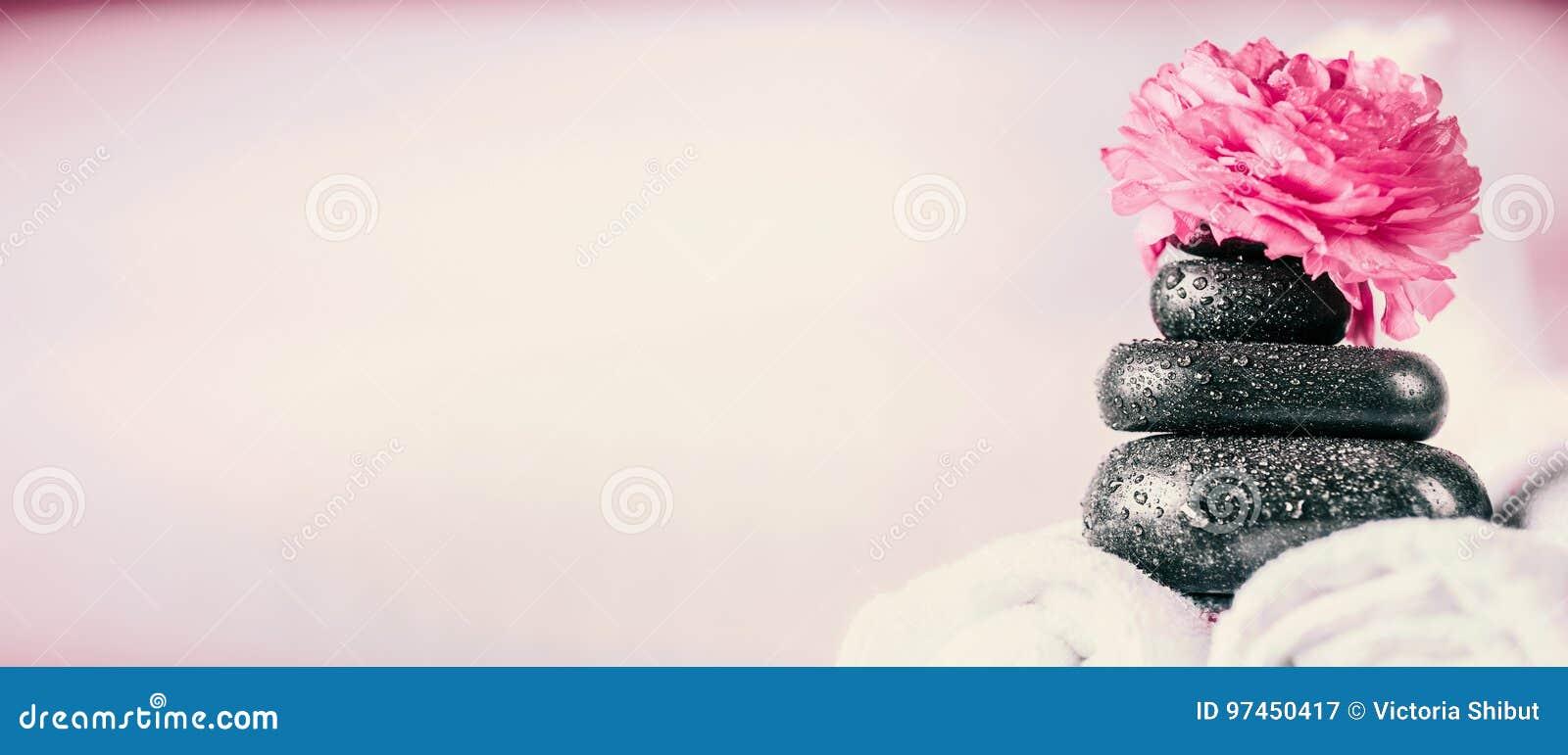 Bunt av brunnsortmassagestenar med rosa färgblommor och handdukar, wellnessbakgrund
