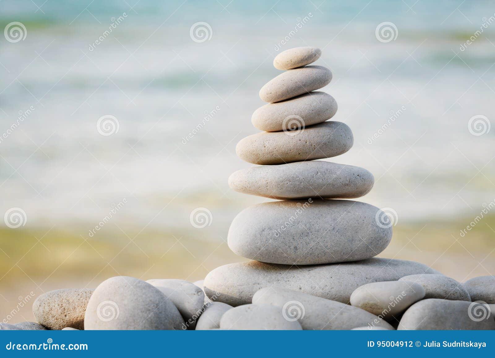 Bunt av den vita kiselstenstenen mot havsbakgrund för brunnsort-, jämvikts-, meditation- och zentema