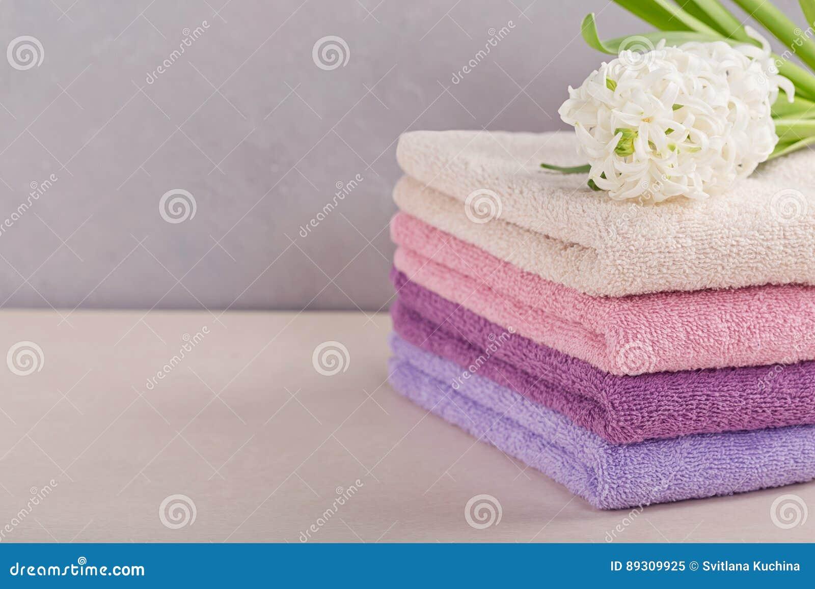 Bunt av färgrika badlakan med hyacintblomman på ljusbaksida