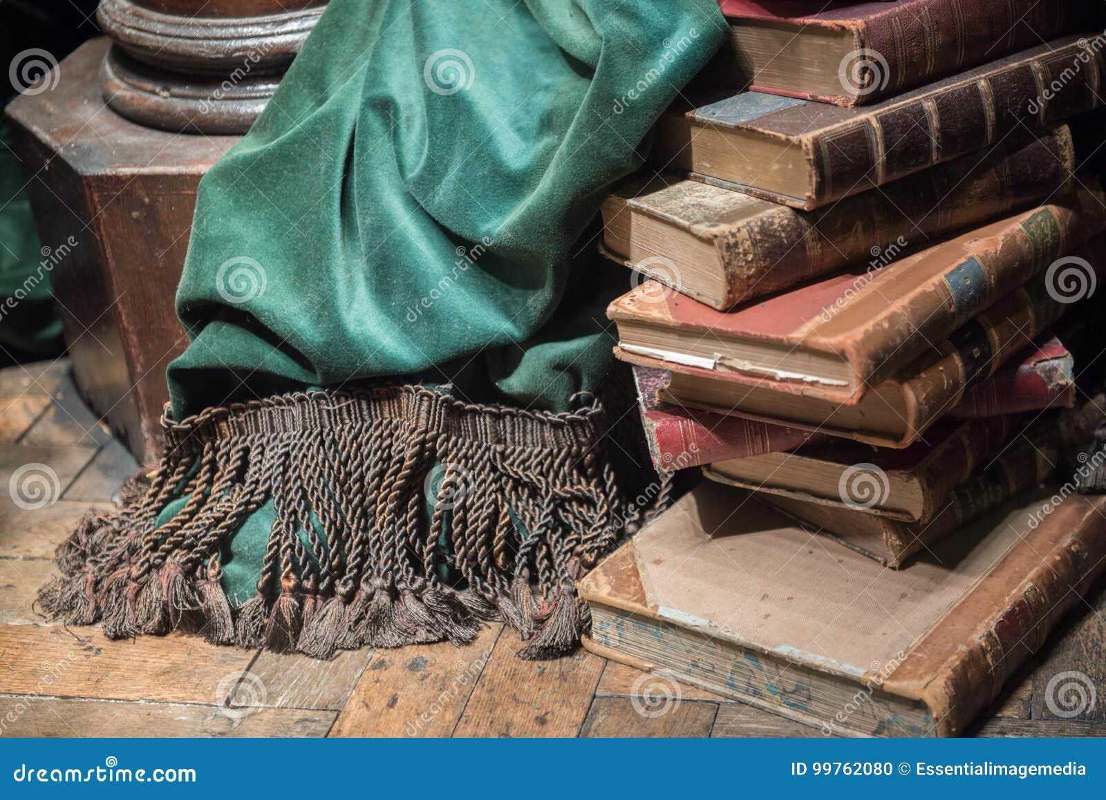 Bunt av gamla böcker med den gröna gardinen