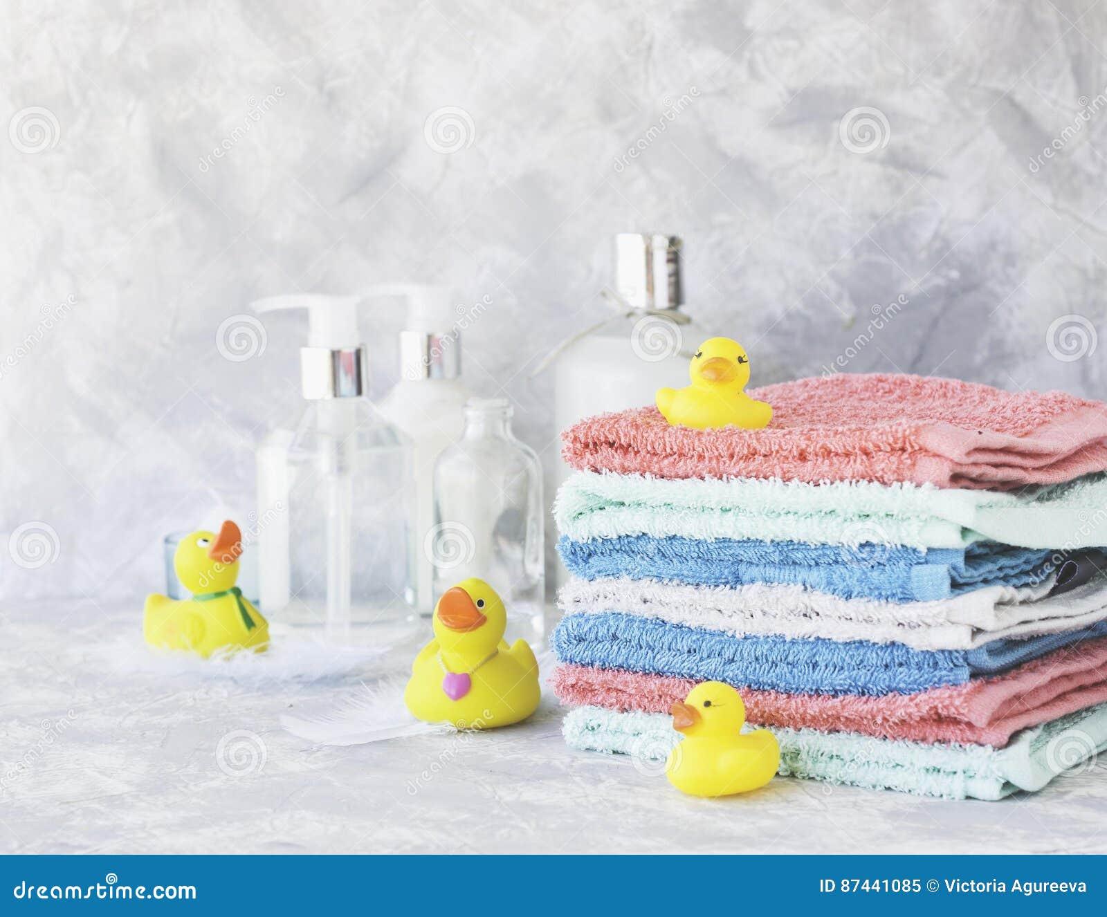 Bunt av handdukar med gula rubber badänder på vit marmorbakgrund, utrymme för text, selektiv fokus