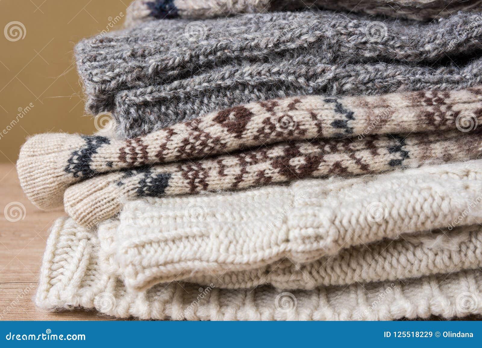 Bunt av handgjorda varma stack tröjor för sockahalsduktumvanten från grova grå färger för beiga för brunt för ullgarn Wood tabell