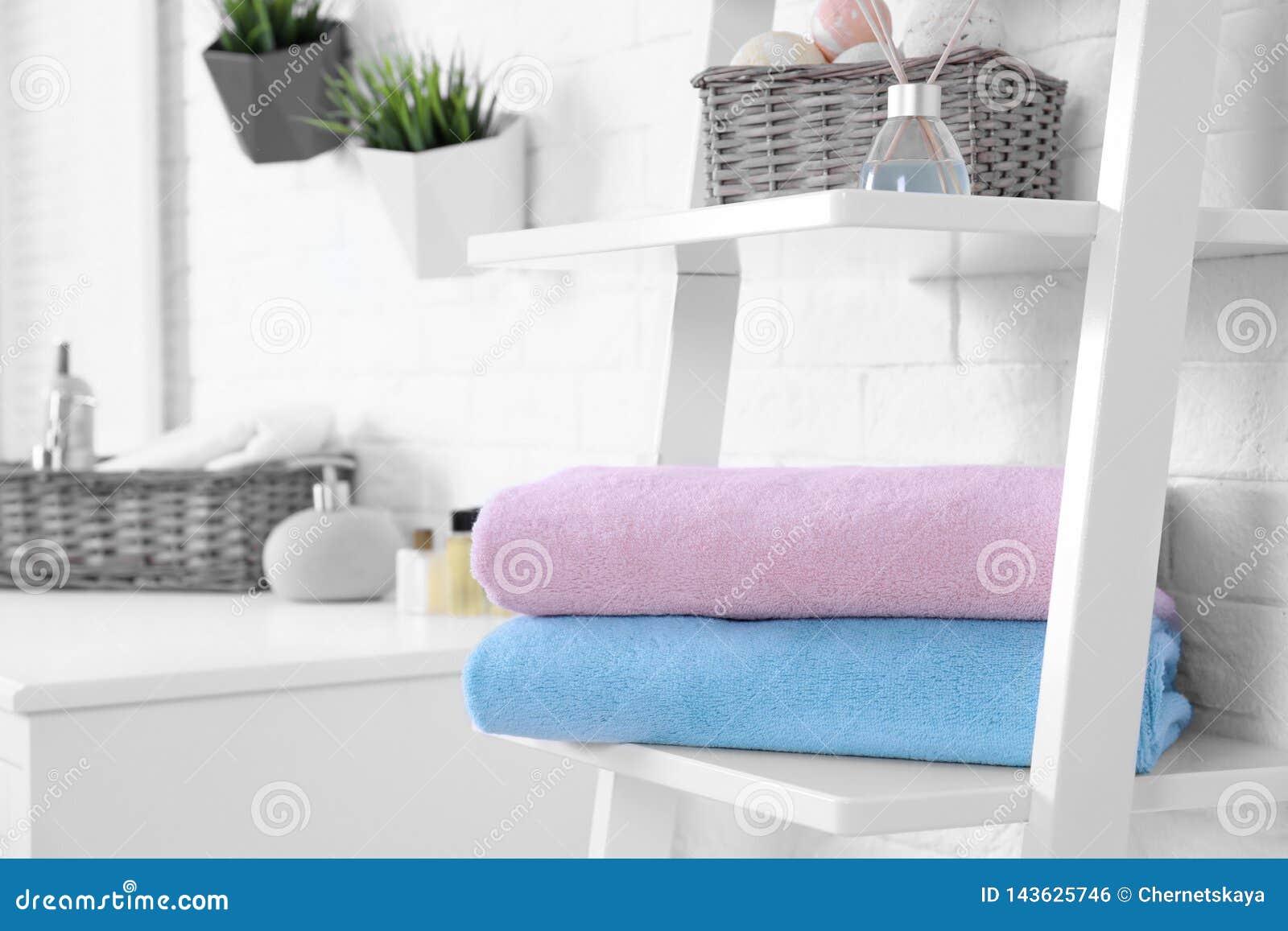 Bunt av nya handdukar på hylla i badrum