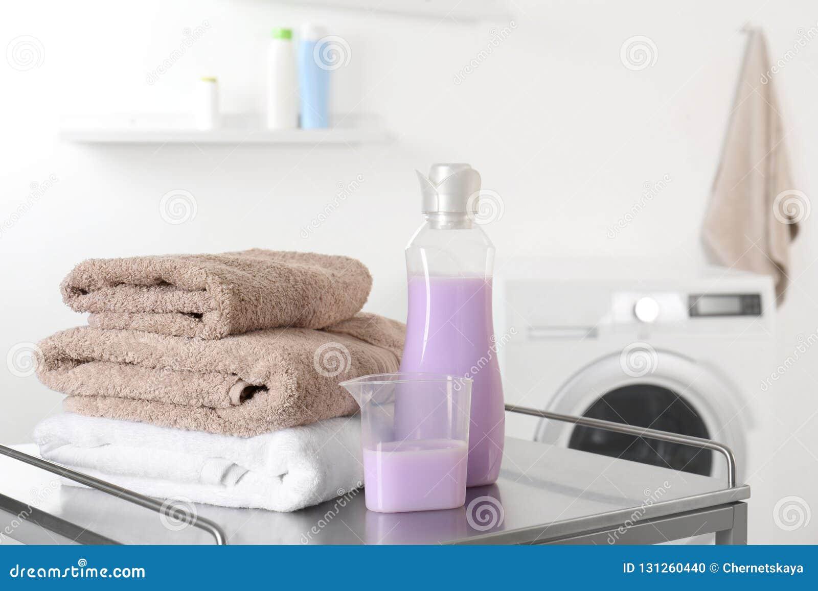 Bunt av rena handdukar och tvättmedel på tabellen