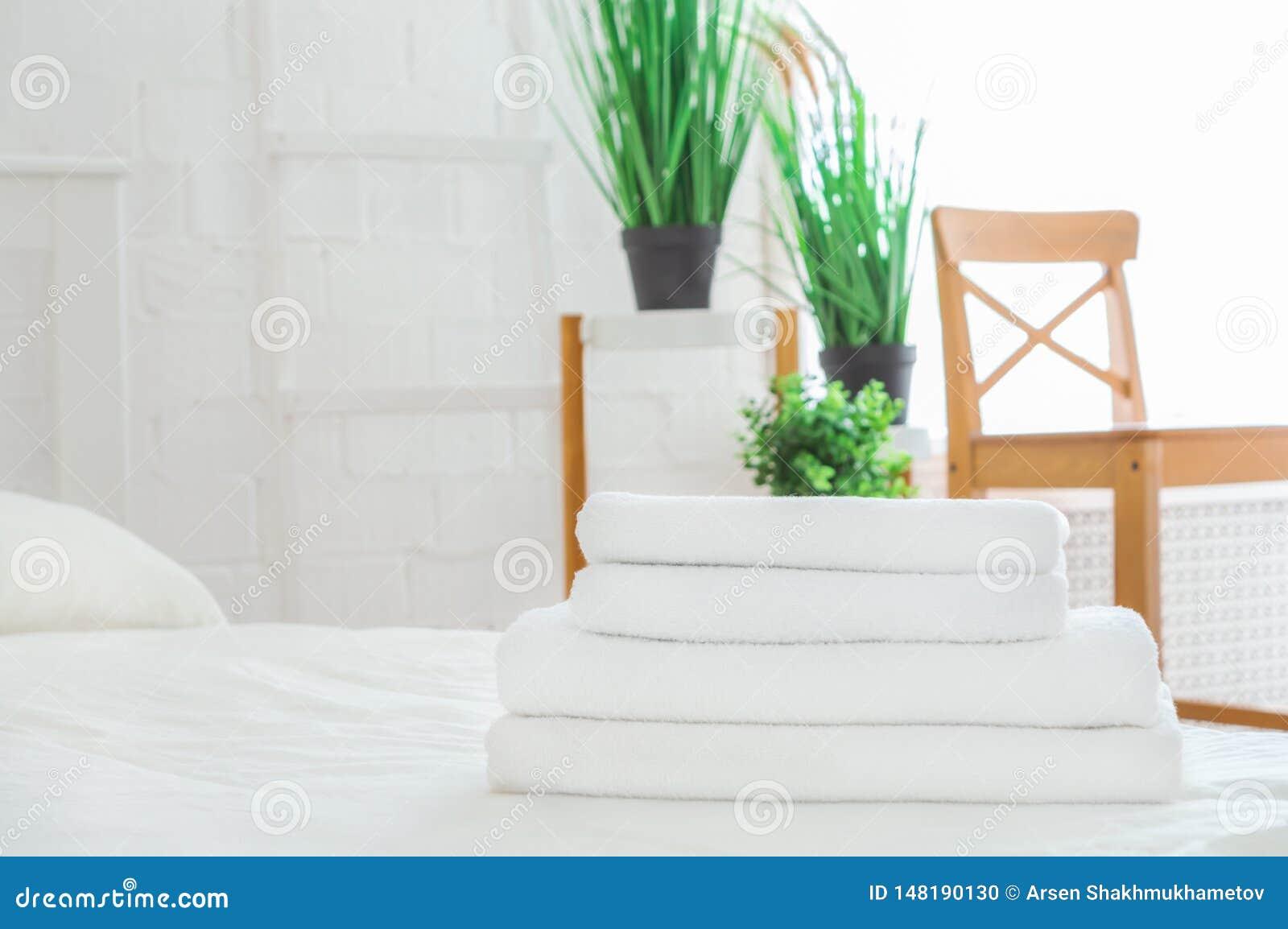 Bunt av rena handdukar på vit säng i rum Utrymme f?r text
