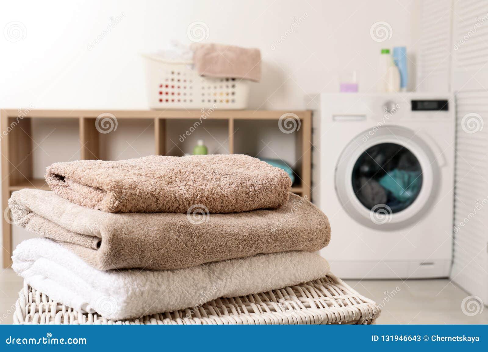 Bunt av rena mjuka handdukar på korg i tvättstuga