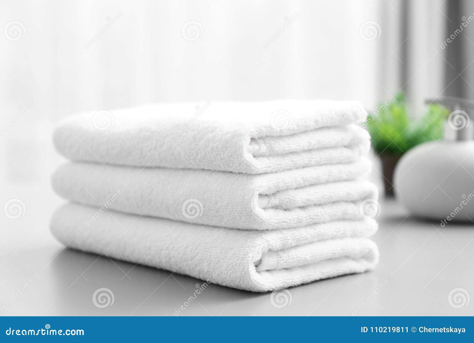 Bunt av vita rena handdukar på tabellen
