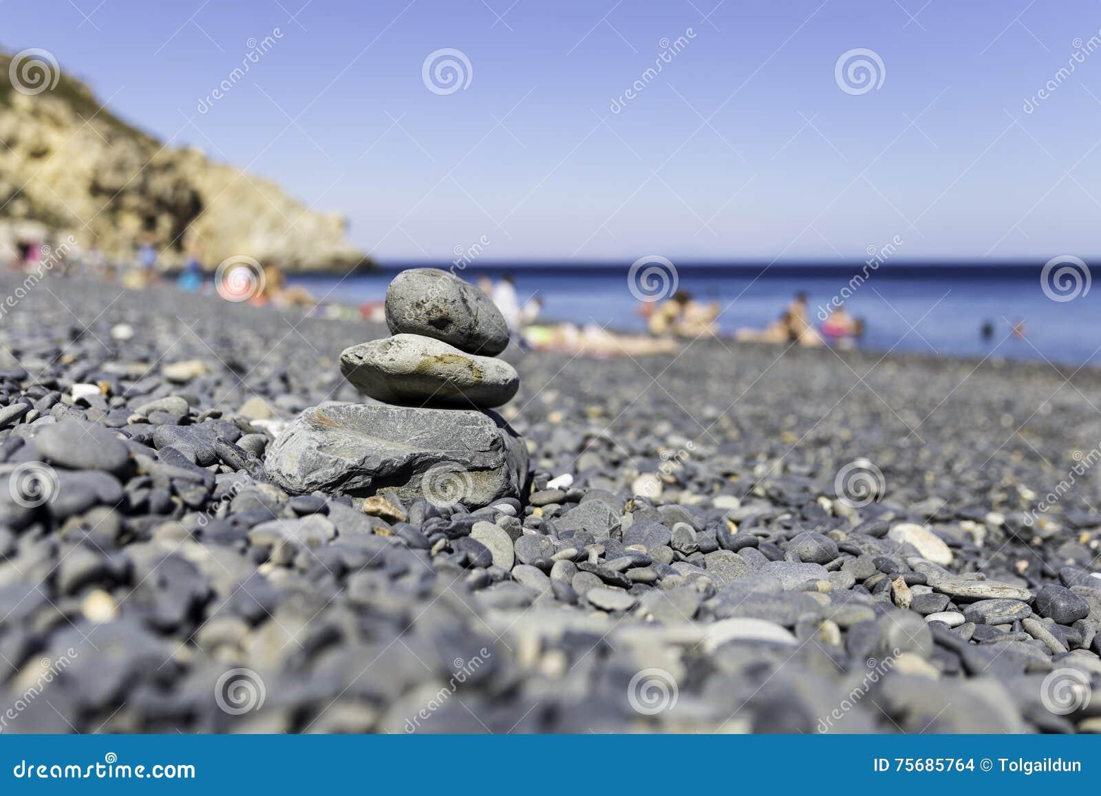 Bunt av zenbrunnsortstenar på stranden för Mavra Volia vulkangrus