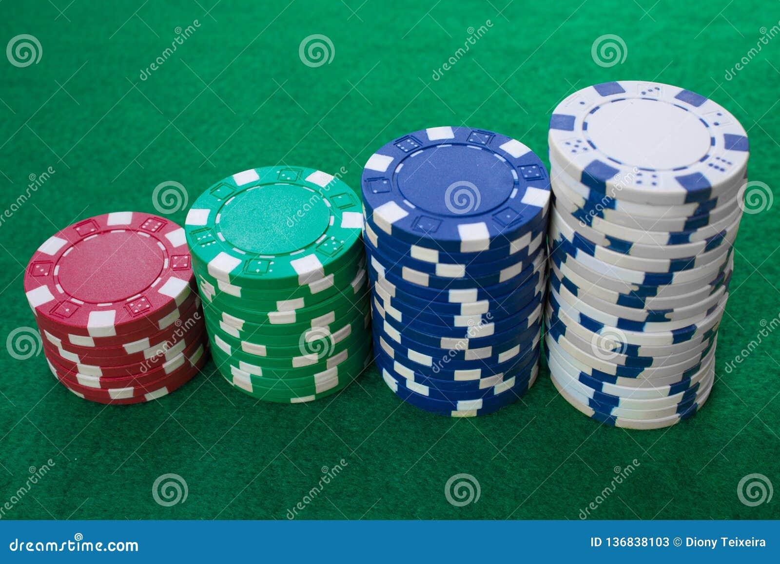 Buntar av pokerchiper inklusive rött, vitt, grönt och blått på en grön bakgrund Vit bakgrund