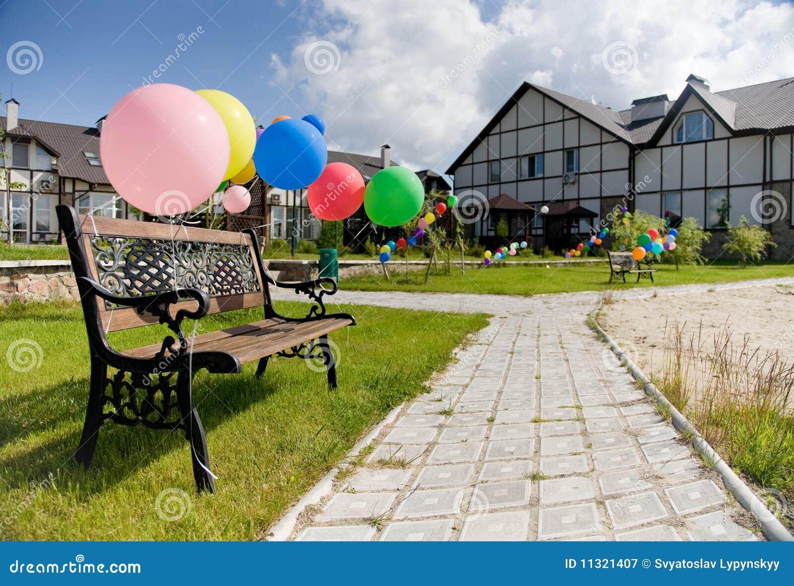 Bunte Ballone nähern sich brench auf Gasse und Häusern