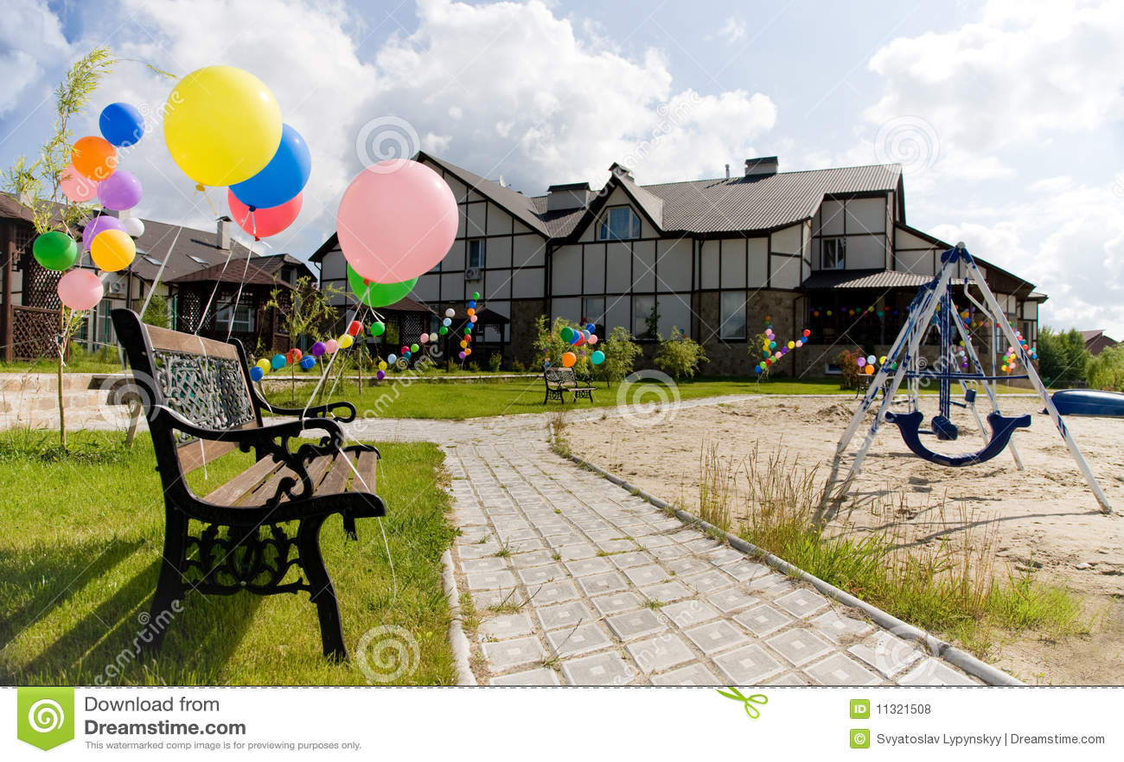 Bunte Ballone nahe Bank auf Gasse mit Schwingen