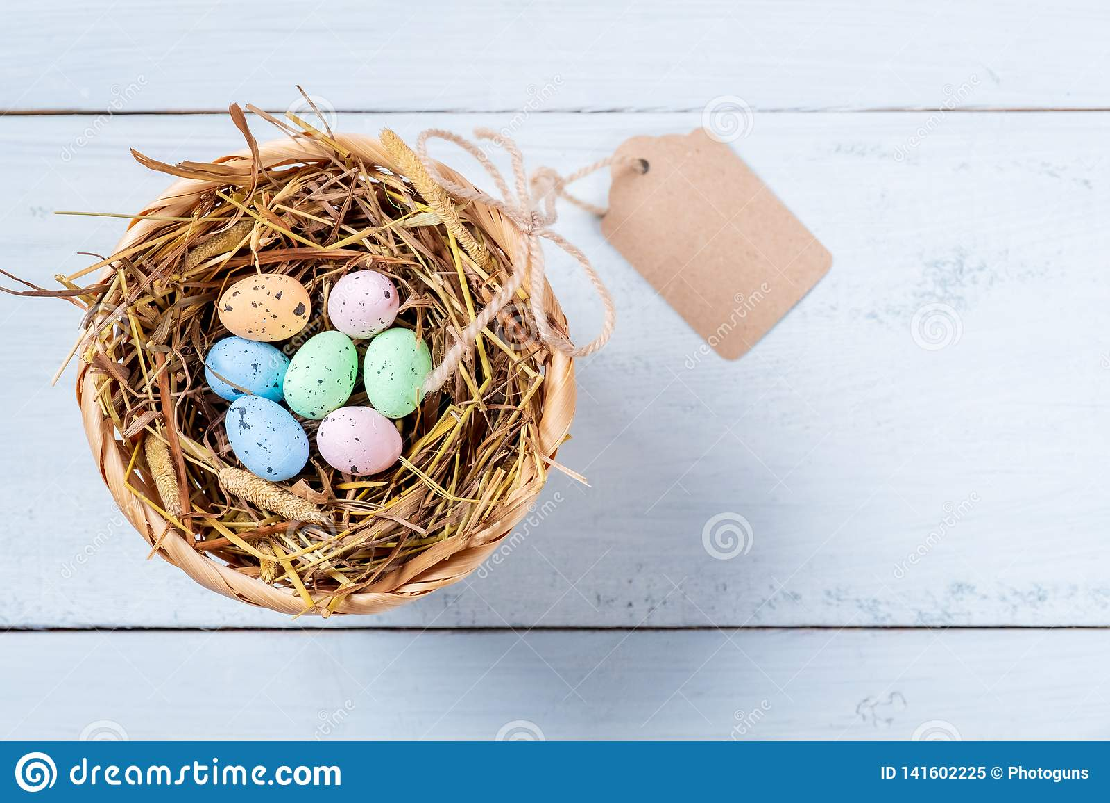 Bunte Easter Eggs im Nest des Strohs mit Umbau auf blauem hölzernem Hintergrund