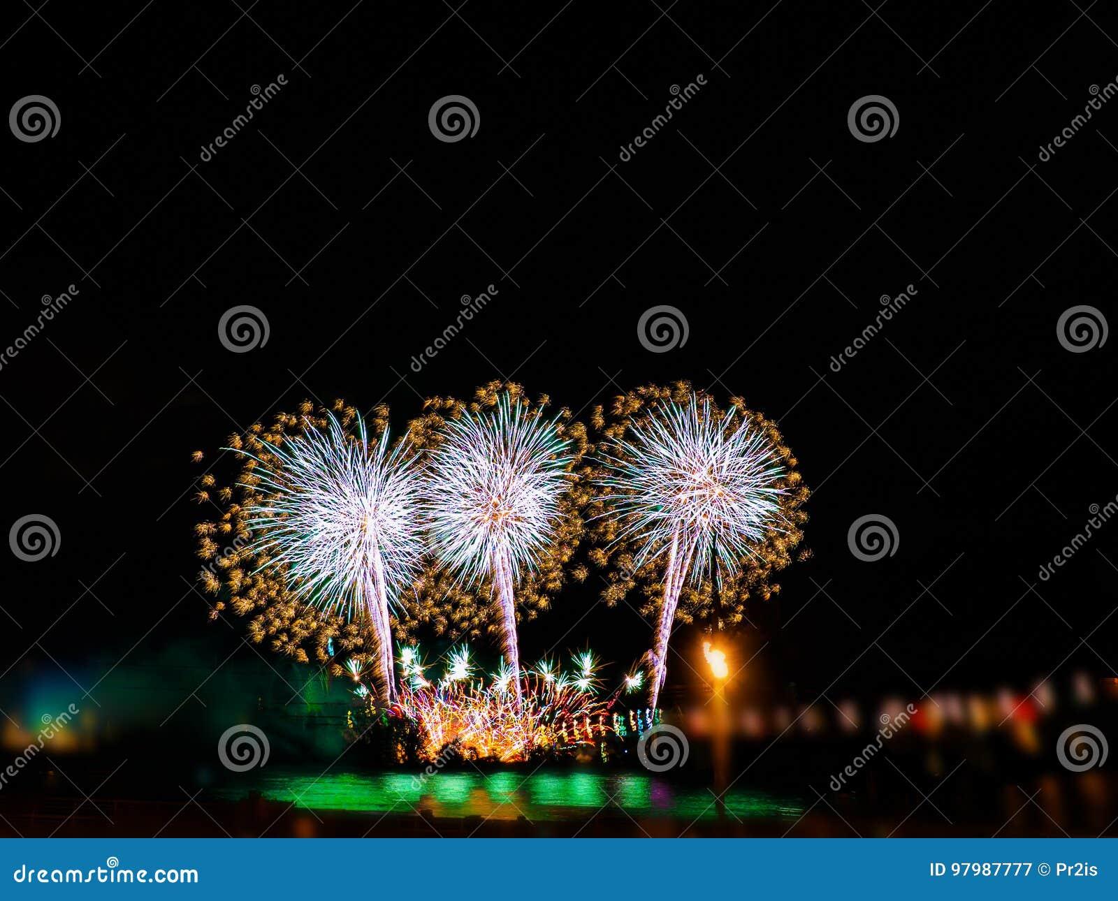Bunte Feuerwerke mit mehrfachen Explosionen gegen bewölkten Himmel