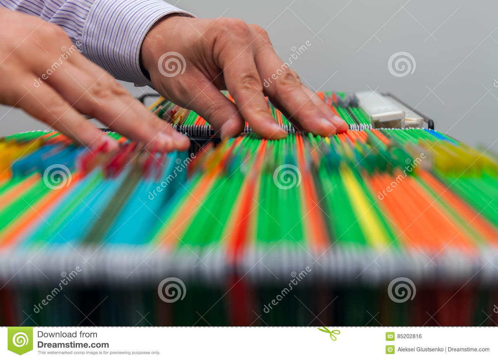 Bunte Hängeregister des abstrakten Hintergrundes im Fach Männliche Hände, die Dokument in einem ganzen Stapel von vollen Papieren