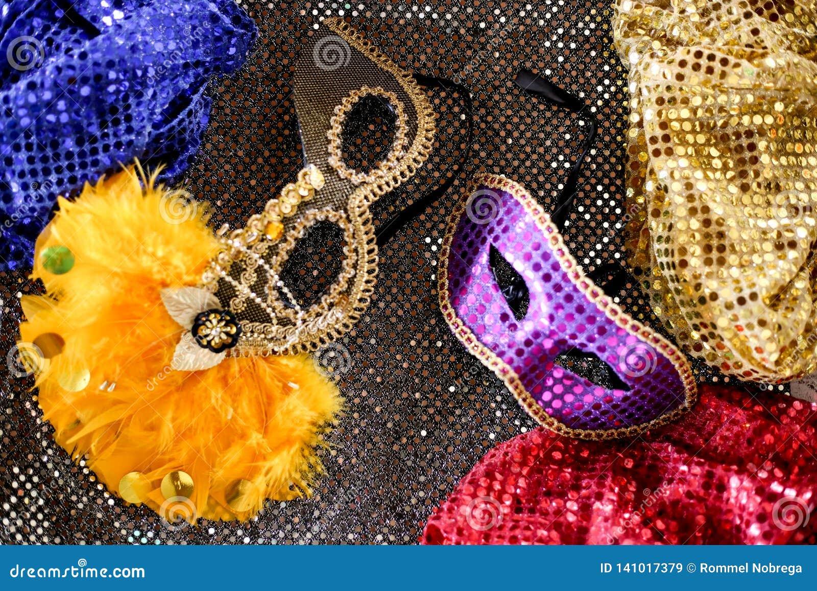 Bunte Karnevalsmasken mit gelben Federn mit dunkelgrauem Hintergrund