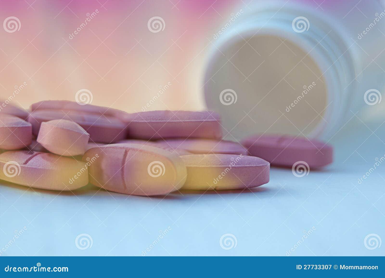 Bunte Pillen auf abstraktem Hintergrund