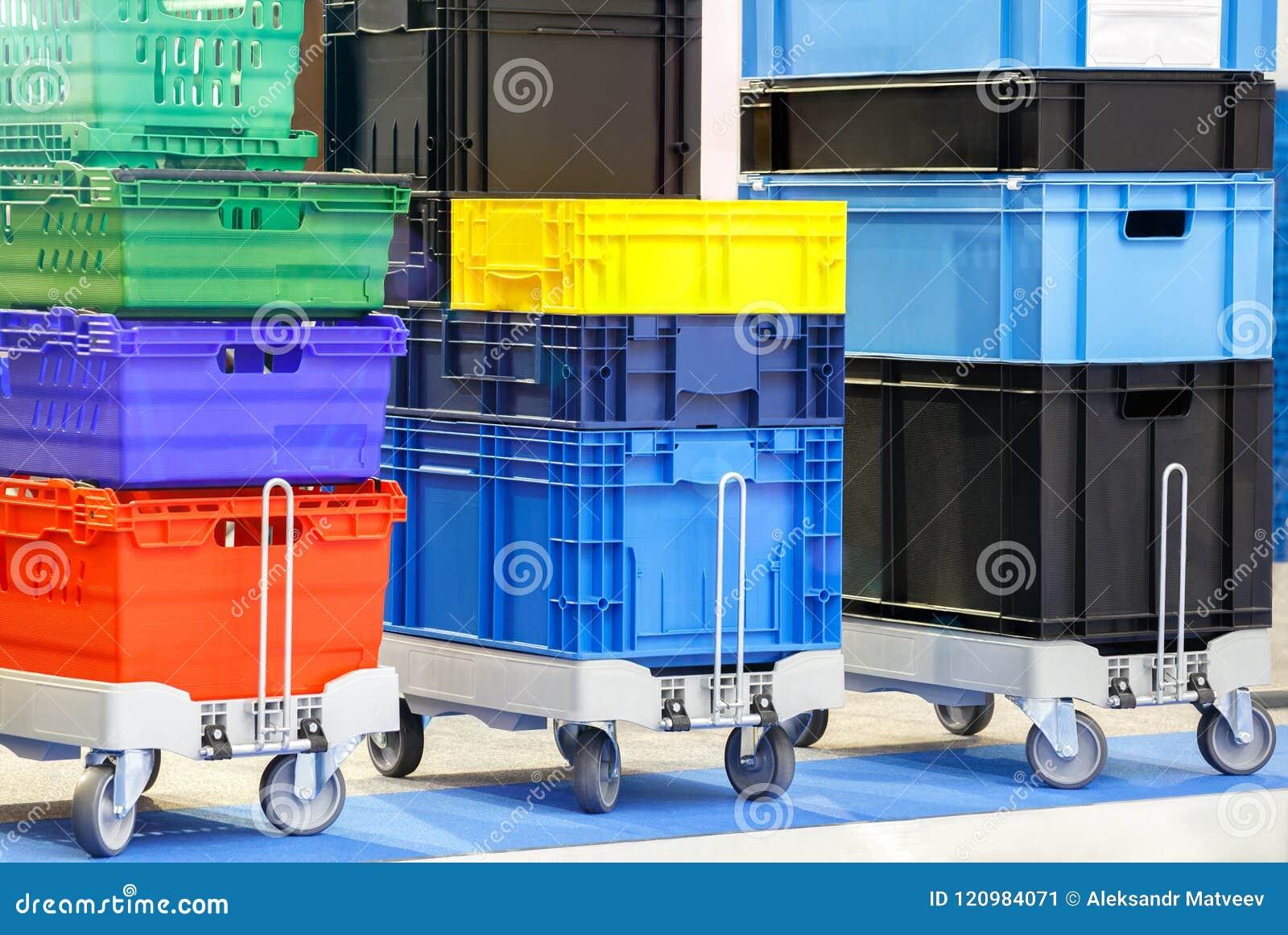 Bunte Plastikkästen stapelten ein nach dem anderen auf Magazinwagen- oder Plattformlaufkatze