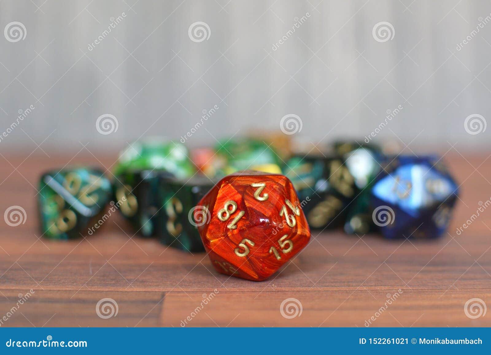 Bunte Rote, Grüne und bue Rollenspielwürfel auf Tabelle mit undeutlichem Hintergrund