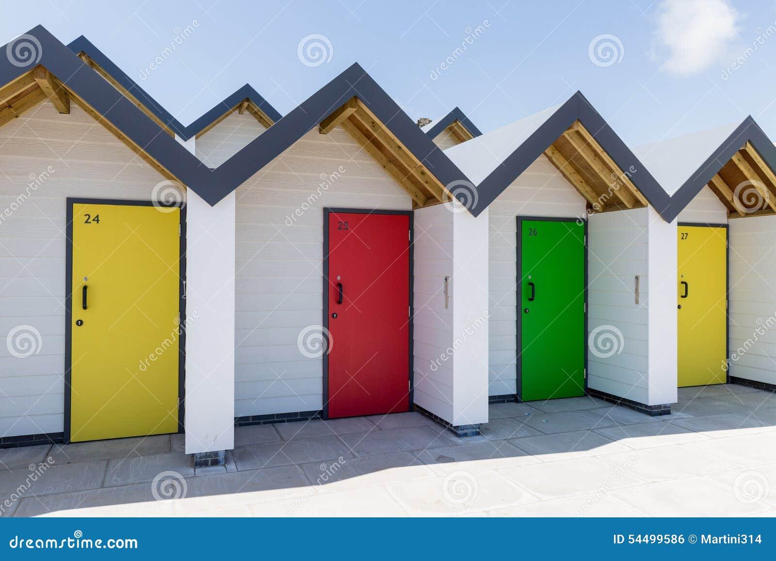 Bunte türen von gelbem von grünem und von rotem wenn jedes einzeln von den weißen strandhäusern nummeriert ist an einem sonni