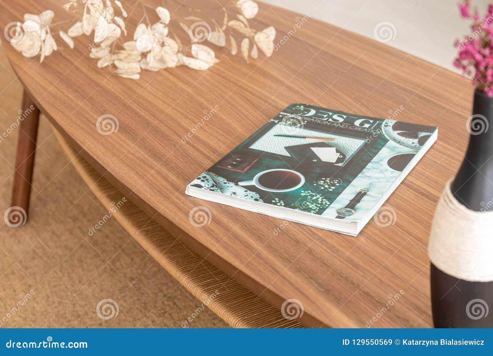 Bunte Zeitschrift auf dem Holztisch im stilvollen Wohnzimmer der modernen Wohnung